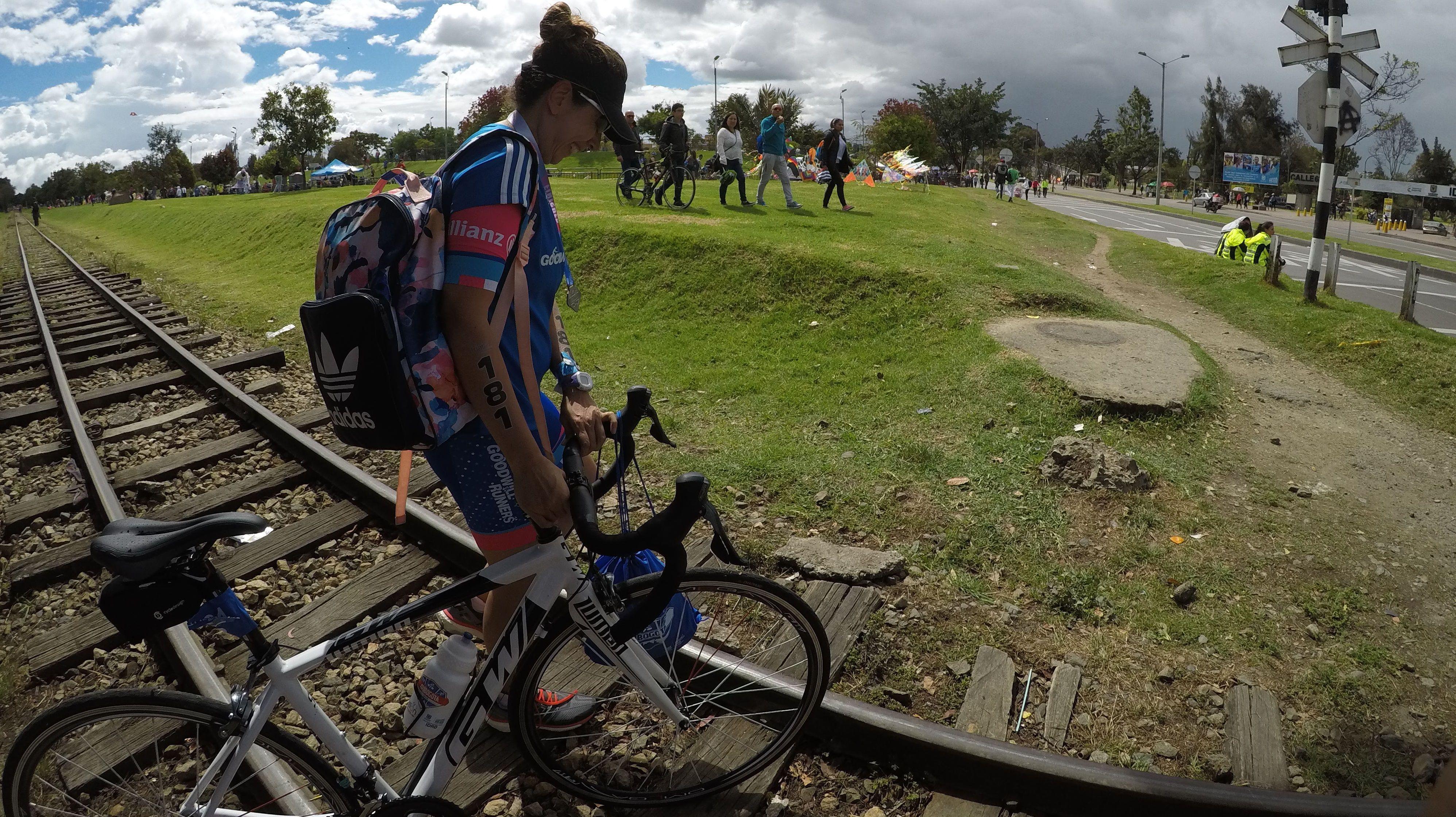 La única meta es la vida. Mujer ciclista camina al lado de su bicicleta cruzando por la carrilera del tren en un día soleado.