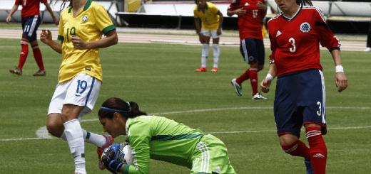 Selección Femenina de Colombia en partido contra Brasil, Copa América 2014, las colombianas visten la camiseta roja y la pantaloneta azul y Brasil con camiseta amarilla y pantaloneta blanca, la arquero Sandra Sepúlveda ataja el balón de frente y la fotografía muestra un congelado mientras cae al piso.